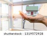 businessman holding house model ... | Shutterstock . vector #1319572928