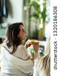 Stock photo beautiful woman laughing and having fun during her coffee time in cafeteria 1320186308
