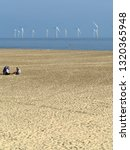 Small photo of Great Yarmouth England August 2018. Portrait view of a wind farm electricity generators in the North Sea. Beach to front with two people thereon. Blue sky.