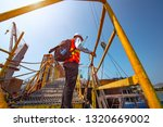 Small photo of ship crew, worker, foreman offshore in replacement or change duty on board the ship or rig station, climbing ladder gangway bridge in high position at risk or danger in working