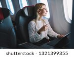 Small photo of Young caucasian smiling female enjoying her comfortable flight while sitting in airplane cabin, listening to music in earphones and drinking water. Wifi internet access on board, passenger near window