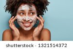 Small photo of Satisfied beautiful black woman makes massage of face, has white foam, problem of wide pores, cares of skin, keeps gaze aside, smiles positively, models over blue studio wall with free space