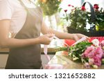 hands of florist in apron tying ... | Shutterstock . vector #1321652882