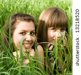 two girls in green grass - stock photo
