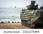The Assault Amphibious Vehicle (AAV) formerly known as Landing Vehicle, Tracked, Personnel-7 that use in the Marine Corps rest on the white sand beach with relaxing soldier background