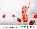 Strawberry milkshake with whipped cream and berry syrup in the tall glass on light background.