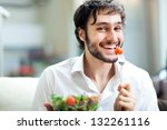 young man eating a healthy salad | Shutterstock . vector #132261116