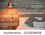 Small photo of Modern Bedroom with rustic wooden headboard and white linen and pillows, copper lamp shade - Airbnb accommodation