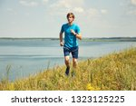 athletic young jogging man... | Shutterstock . vector #1323125225