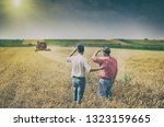 two farmers standing on wheat... | Shutterstock . vector #1323159665