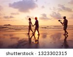 filmmaker filming video of couple with camera stabilizer on the beach at sunset, professional videographer working on film - stock photo