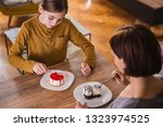 daughter and mother sitting by... | Shutterstock . vector #1323974525