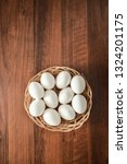 Small photo of many white eggs lie in Round wicker basket on wooden uncouth Board, rustic background, top view, copy space