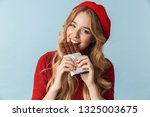 Stock photo image of joyful girl s wearing red beret eating chocolate bar isolated over blue background in 1325003675