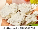 cottage cheese on kitchen table.... | Shutterstock . vector #1325144708