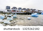 Modern buildings and small cottages with icebergs drifting in the lagoon, Nuuk old city harbor, Greenland