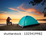 family resting with tent in... | Shutterstock . vector #1325419982