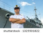 Small photo of Captain standing in dock before warship and looking ahead. A sailor officer in white uniform stands beside battleship.