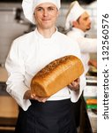 Smiling male chef showcasing freshly baked whole grain bread with sesame toppings. - stock photo