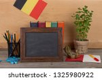 Education concept - blank blackboard, flag of the Belgium, books, chancellery on table and wooden background