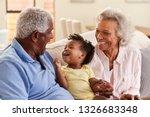 Grandparents Sitting On Sofa A...