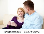 Happy couple sitting together on sofa - stock photo