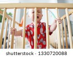 Small photo of A cranky baby boy in his cot
