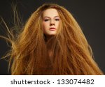 portrait of young beautiful curly red-haired woman posing on gray - stock photo
