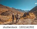 two hikers stands on big rock... | Shutterstock . vector #1331161502
