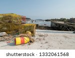 Small photo of Lobster traps sit next to harbor at low tide. There is a floater attached by a rope. The floaters are color coded so the lobster fisherman can identify their traps in the ocean.