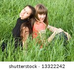 two beauty girlfriends sitting in grass - stock photo