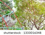 Top of colorful ferris wheel with background of big green trees