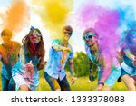 Small photo of Cheerful and happy soiled friends throw bright paints on camera and smiling. Company of young people in sunglasses having fun with holi paints on spring summer festival. Holi party concept.