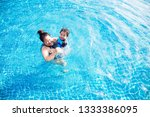 mother and baby swim in the pool | Shutterstock . vector #1333386095