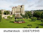 Small photo of Bath England Nay 2017. Parade Gardens. Looking across green grass park to six story Bath stone flats. Bandstand in park surrounded by flowers. Trees in leaf. One deck chair. High white cloud.