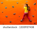 girl climbing on a wall in... | Shutterstock . vector #1333937438