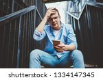 worried young man holding phone ...   Shutterstock . vector #1334147345