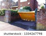 yellow rubbish skip on driveway.... | Shutterstock . vector #1334267798