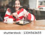 happy girl eating a cake in a... | Shutterstock . vector #1334563655