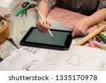 designer draws new clothes  | Shutterstock . vector #1335170978