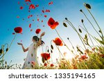 girl stands in poppy field | Shutterstock . vector #1335194165