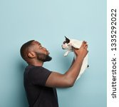 Stock photo little puppy finally finds new home caring dark skinned man stands sideways holds small french 1335292022