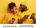 Small photo of Surprised curious dark skinned woman looks at screen of boyfriends cellular, reads online post with interesting content, excited with smartphone or app features, isolated over yellow background.