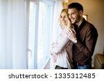happy loving couple near window ... | Shutterstock . vector #1335312485