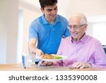 male care assistant serving... | Shutterstock . vector #1335390008