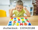 thinking little boy solve puzzle | Shutterstock . vector #1335420188