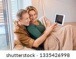 happy couple using digital... | Shutterstock . vector #1335426998