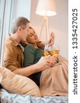 happy couple holding glasses of ... | Shutterstock . vector #1335427025