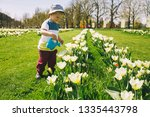 little boy in beautiful garden... | Shutterstock . vector #1335443798