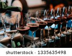 bartender pours red wine in... | Shutterstock . vector #1335635498